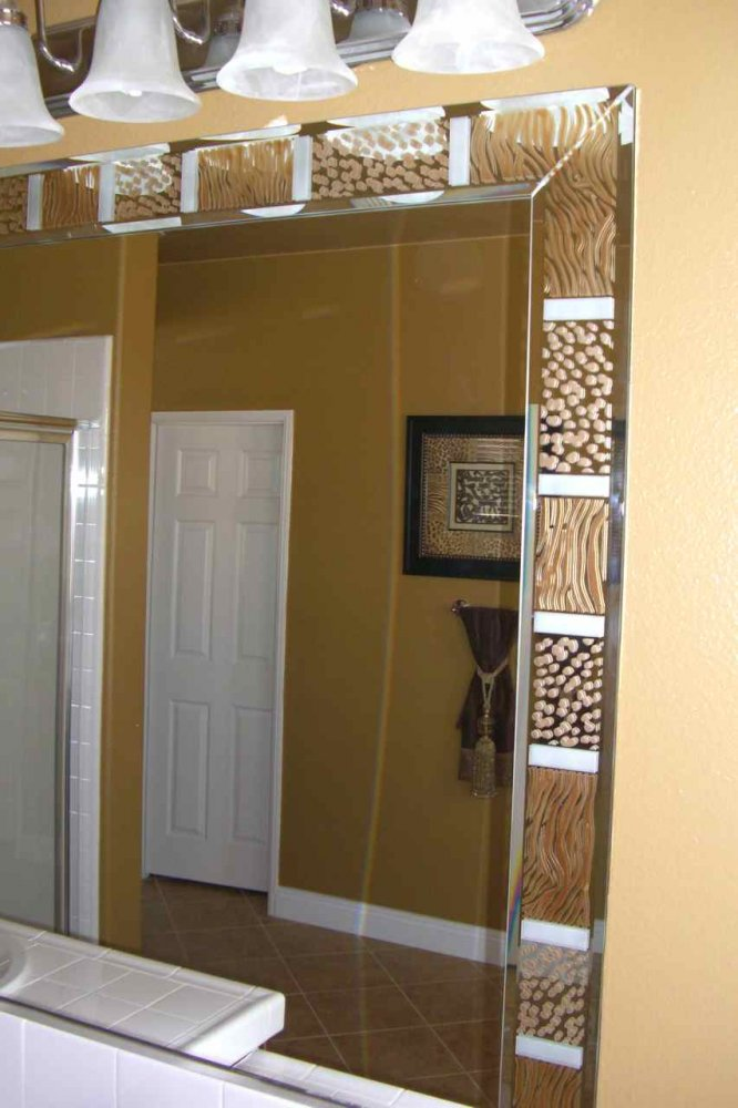 Custom beveled mirror strips, overlay pieces on the mirror border that have been etched, carved and painted in animal print motif.
