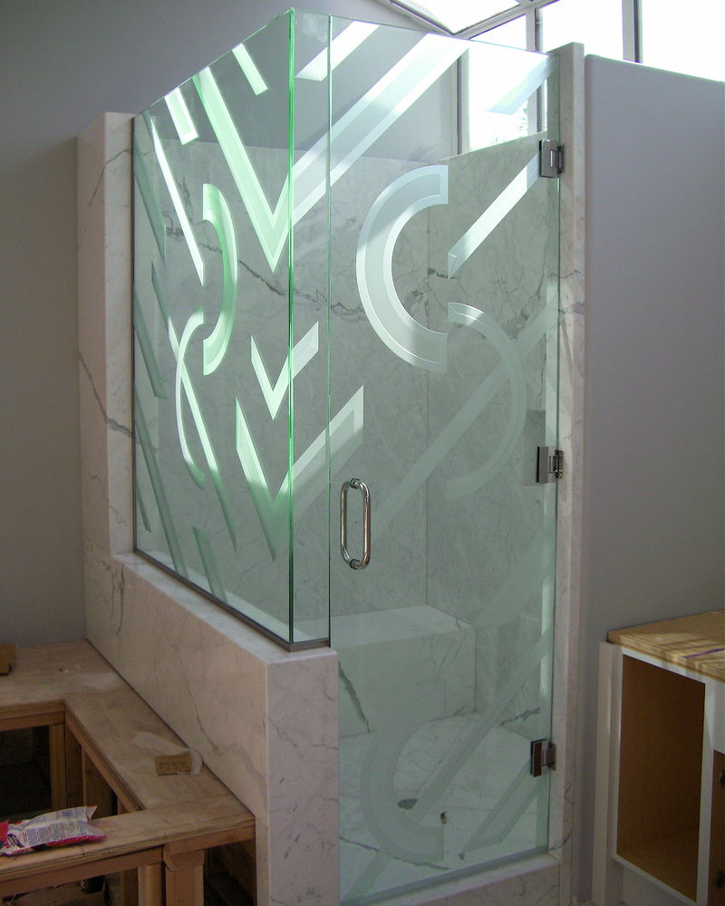 "Decorative Glass Shower Enclosure.  Carved and etched glass half circles and diaganol bands.  Outside edges are sculpture carved, insides of the shapes are lightly etched, or ""misted""."